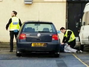 Officers detain a man on the ground following the discovery.